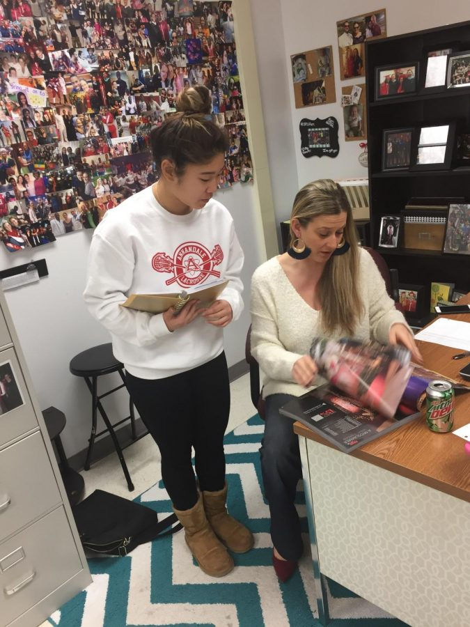 McKenzie Yi and senior class sponsor Whitney Hardy look over catalogs for ideas.