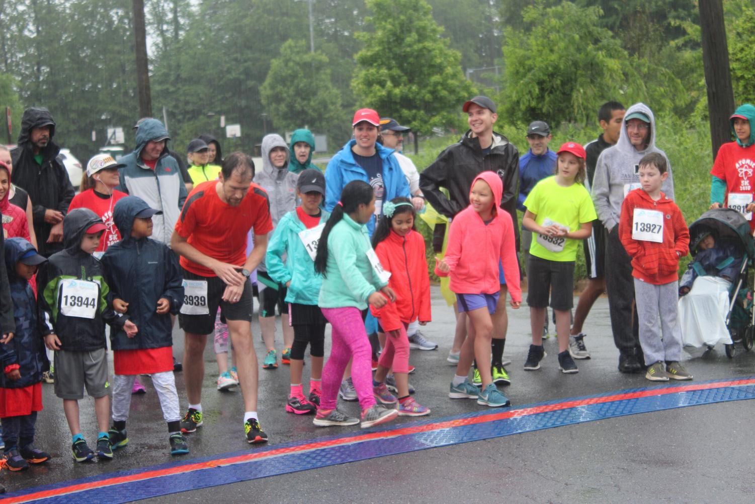 About 50 participants lined up in the rain at the starting line in the annual Atoms 5K race. The first place runner crossed the finish line at about 17 minutes.