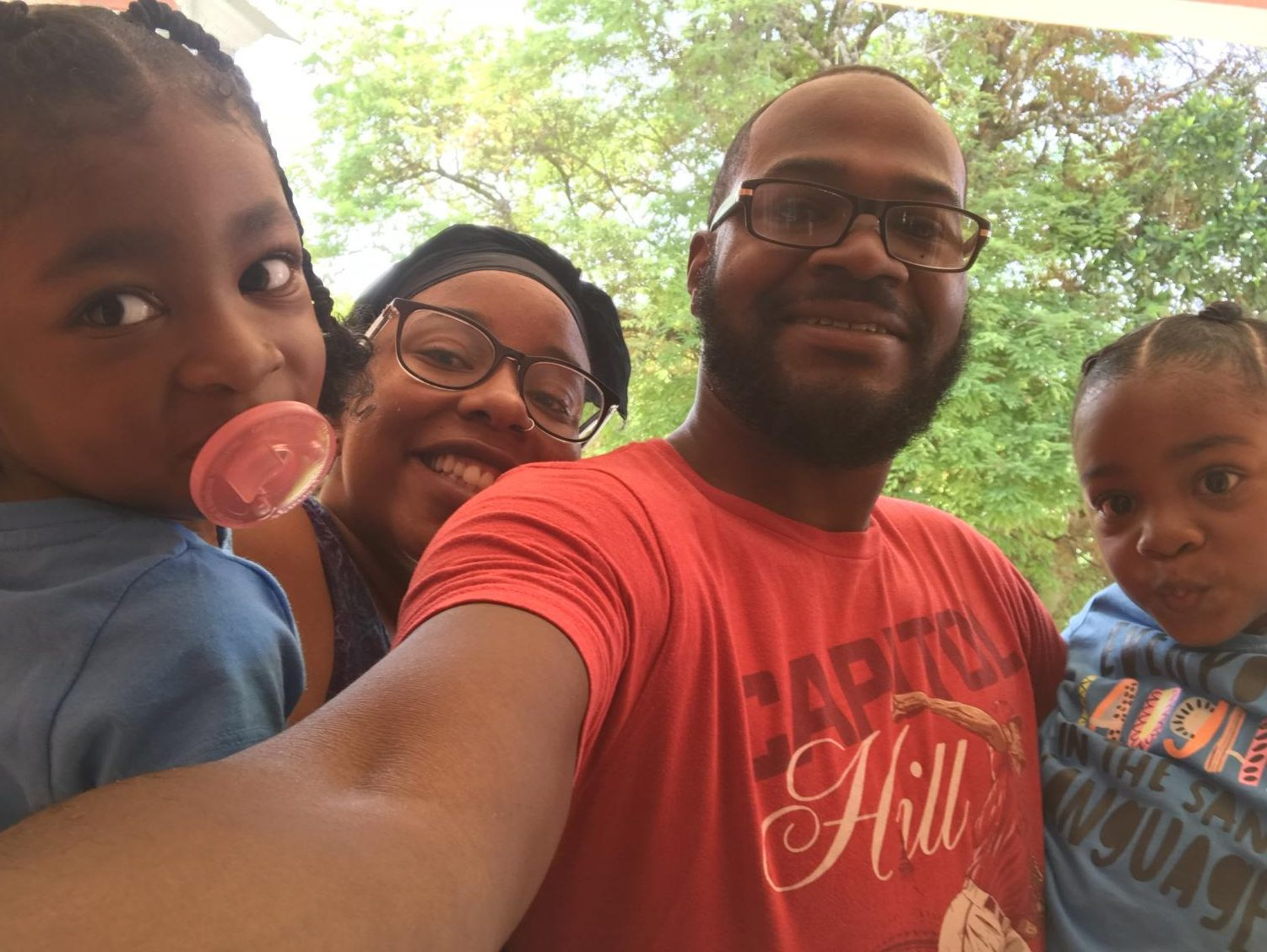 Desrivieres takes a picture with his wife and two kids outside of his house in Jamaica over the summer.