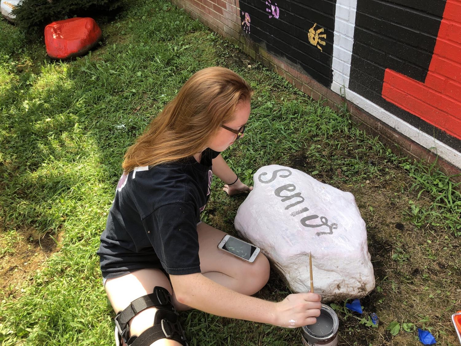 Senior Alison Scott paints a Class of 2019 motto on a rock in the senior courtyard on Aug. 14.