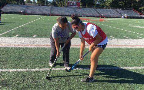 Coach Corin helps Elizabeth Ortiz with handling a stick.