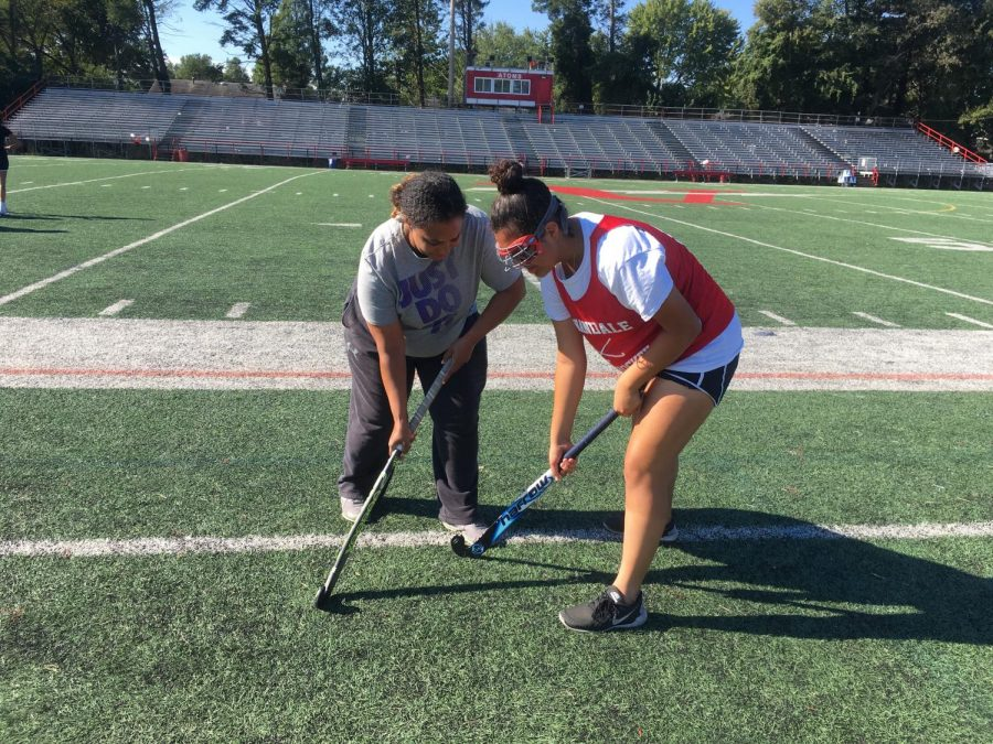 Coach+Corin+helps+Elizabeth+Ortiz+with+handling+a+stick.