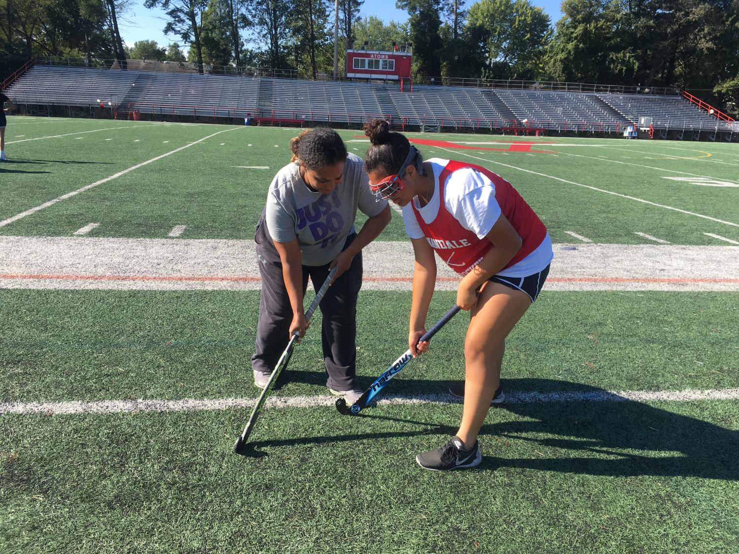 Coach Corin helps Elizabeth Ortiz with handling a stick.