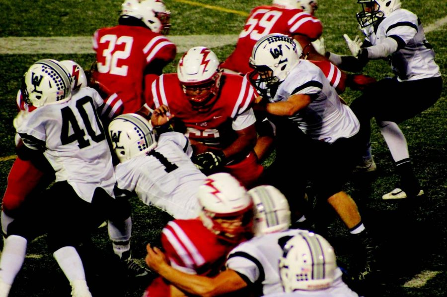 Junior offensive lineman, Brian Fuentes-Llanes (62) heads in for the block against Washington-Lee on Sept. 18