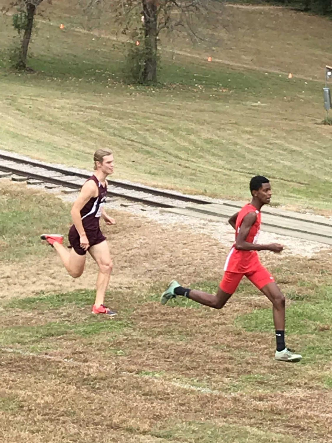 Junior Mikyas Sahlu kicks away from Mount Vernon's senior runner, Hunter Fowlie, during the end of the race to win the Gunston District Championship.