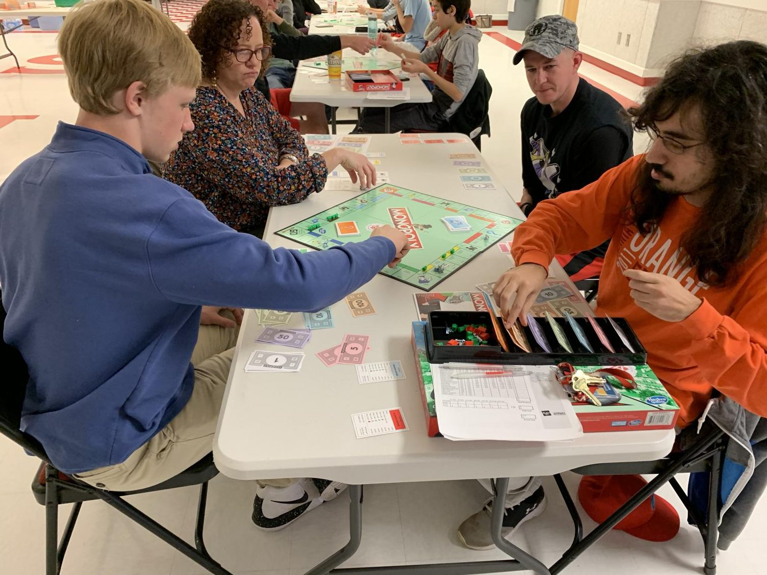 Senior Alex Bellem (left) moves his piece on the Monopoly board after a turn and Math teacher Evaristo Martins (Right) deals money as the broker for the first round of the day at the Monopoly tournament.