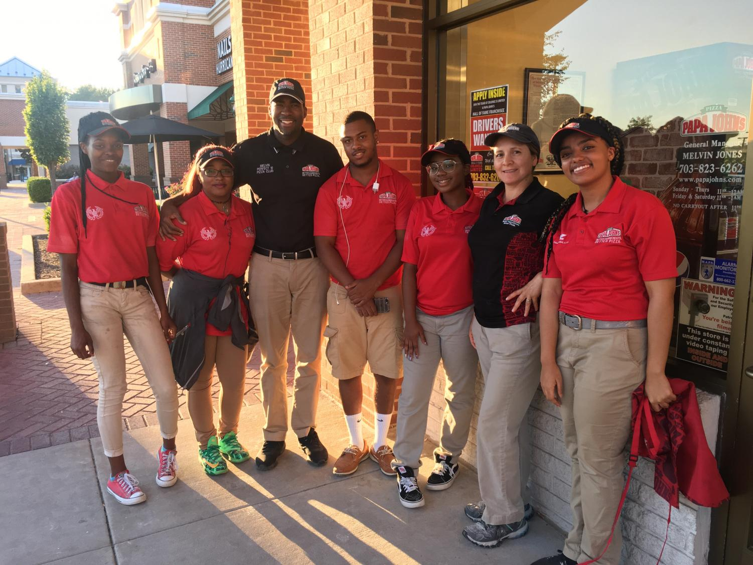 Senior Hemen Besufekad (right) stands in front of Papa John's, where she worked for the summer, with her coworkers.