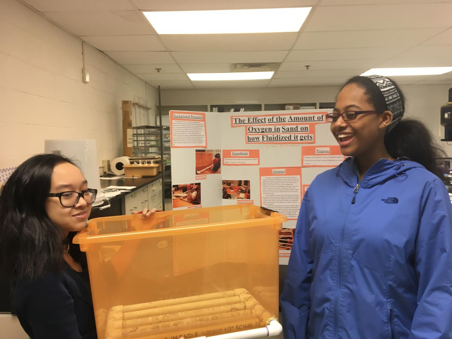 Sophomores Han Le and Haleluya Worku practice presenting for the science fair. Le is pictured holding the fluidized bed from her project.