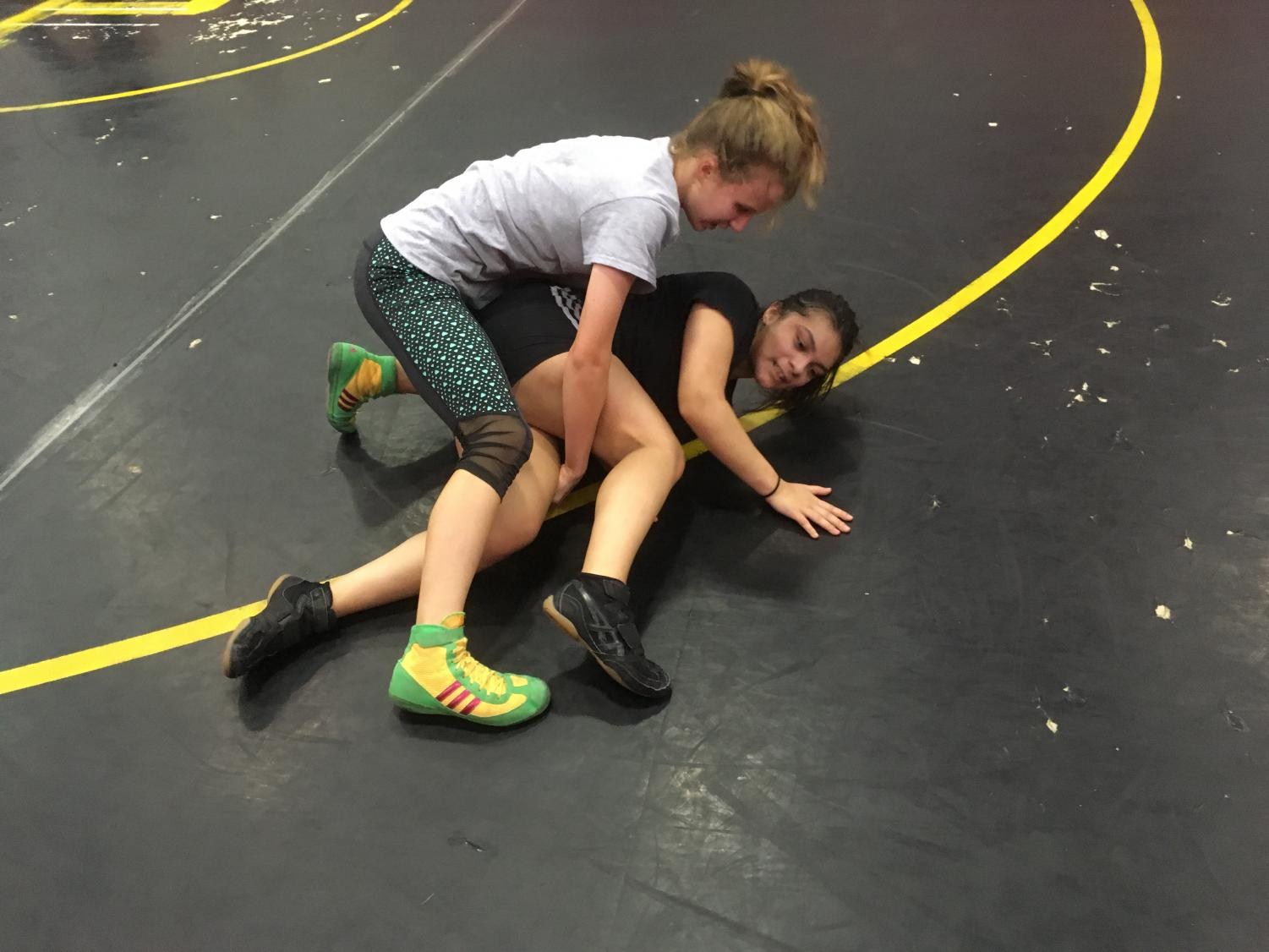 Sophmore Eva Gomez graples sophmore Breanna Sanchez during a AHS varisty wrestling practice.