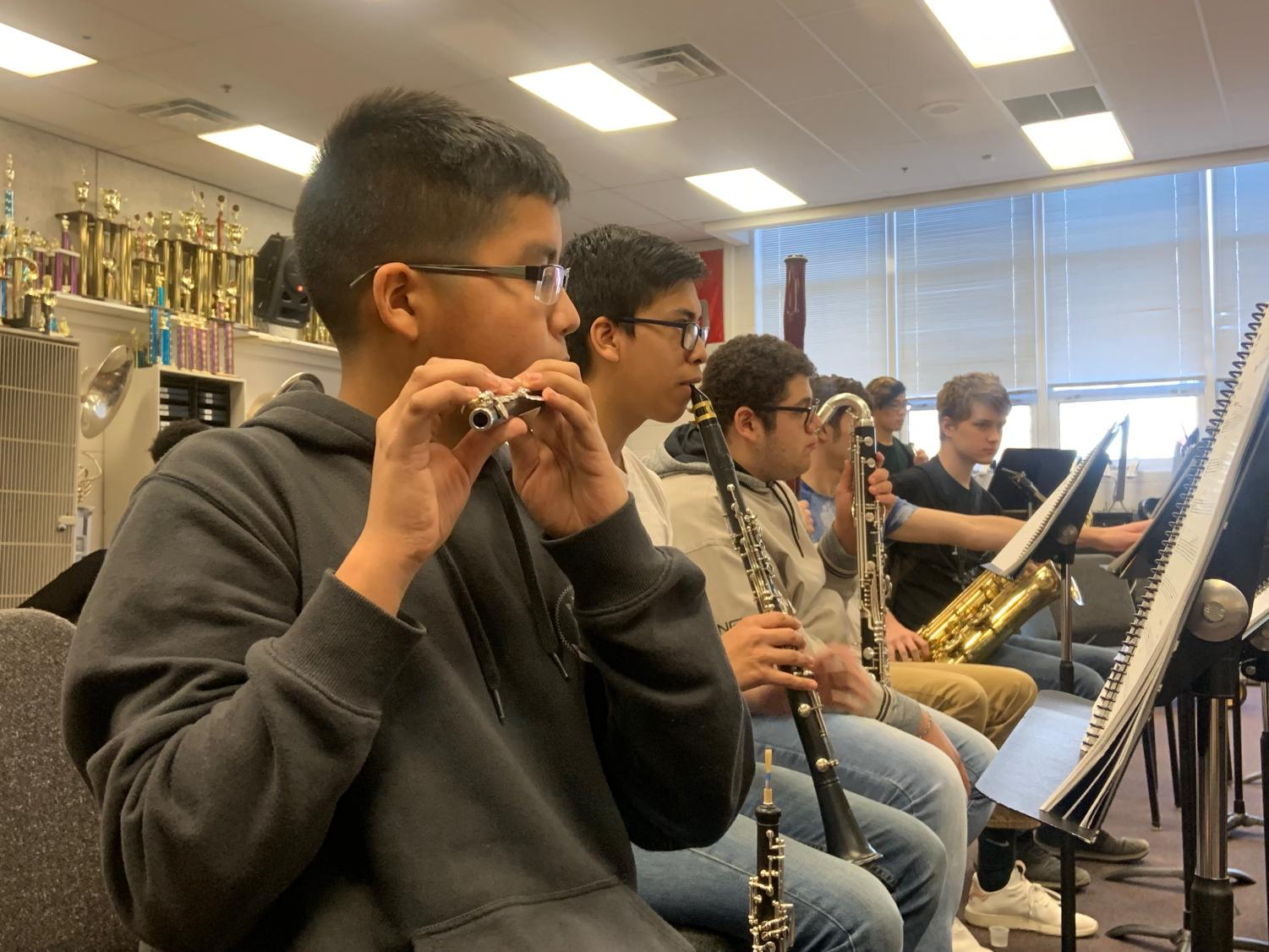 Freshman Andrew Zurita plays the flute during the pit rehearsal.
