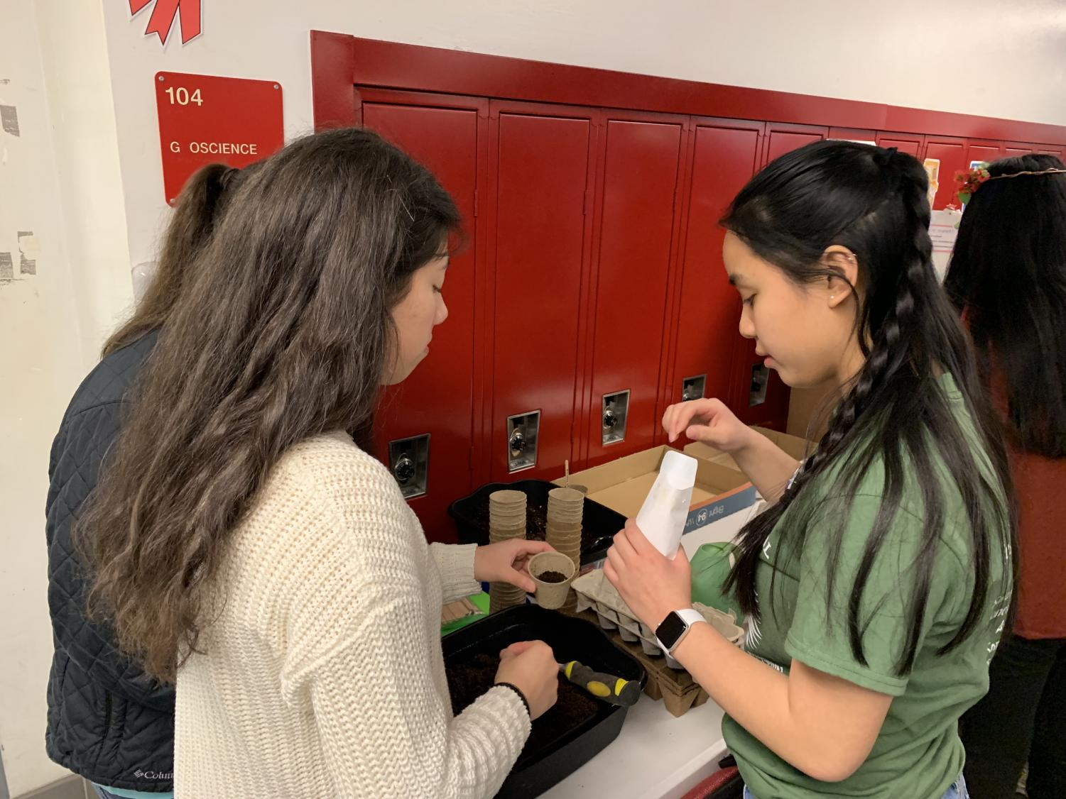 Seniors Alondra Gonzalez (Left) and Danica Tran (Right) plant seeds at the Green Atoms booth at the Just World Festival.