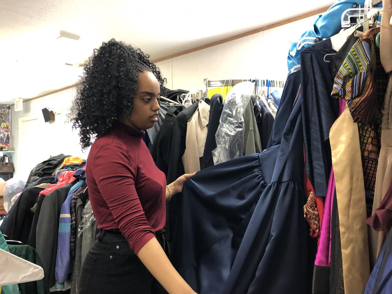 Senior Hemen Besufekad looks at donated prom dress in the Parent Resource Center. Pop-up shop will begin Wed. March 20 from 3 p.m. to 6 p.m. and Thurs. March 21 from 6 p.m. to 8 p.m.
