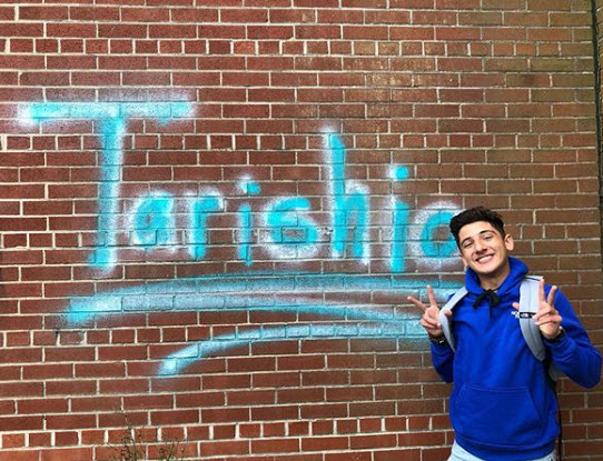 Darwiesh poses with his pseudonym, Tarishio, which is spray-painted on the wall at the senior courtyard.