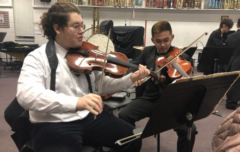 """Junior viola player Freddy Henriquez-Pinzon and sophomore viola player Matthew Kim practicing Waltz No. II by Dimitri Shostakovich, Arr. By Paul Lavender, beofre perfoming on stage. """"I like Waltz No. II because it's a very technical piece and it's fun to play,"""" Henriquez-Pinzon said."""