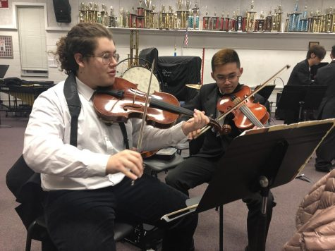 "Junior viola player Freddy Henriquez-Pinzon and sophomore viola player Matthew Kim practicing Waltz No. II by Dimitri Shostakovich, Arr. By Paul Lavender, beofre perfoming on stage. ""I like Waltz No. II because it's a very technical piece and it's fun to play,"" Henriquez-Pinzon said."