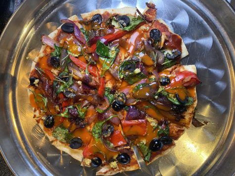 Junior Danya Khreshi makes a vegan pizza topped with olives, peppers, onions, spinach and buffalo sriracha.