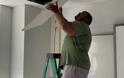 Instructional assistant Khalid Mohammed fixes the ceiling in an AHS classroom. Many improvements have been made around AHS to prepare the school for when students come back.