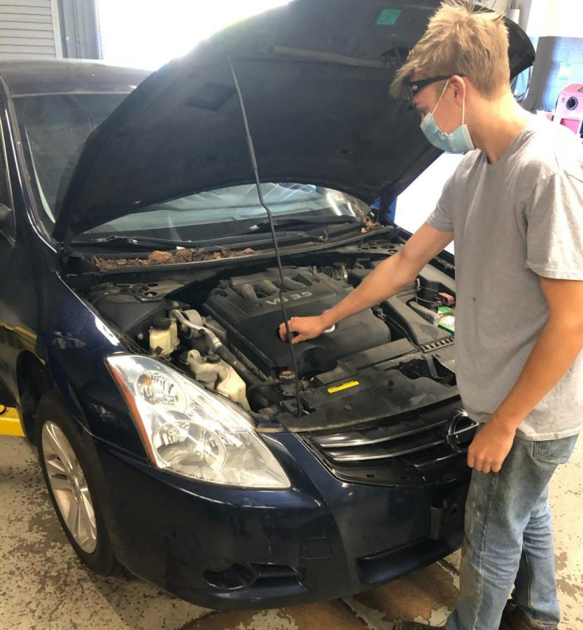 "Senior Nicholas Pemberton works on a car in his Auto Tech class. ""I definitely missed being in the shop,"" Pemberton said. ""It's better than doing the online lessons."" He will continue attending in-person classes on Mondays even though the next group of students is no longer returning to school because of an uptick in COVID-19 cases."
