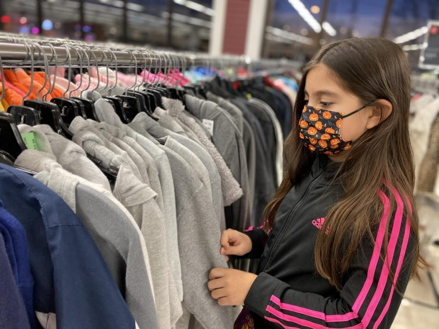 Nine-year-old Jinan Hamadeh looks through the racks at Salvation Army. Children five years old and above must now wear masks in indoor public settings. The previous regulation was for ten years old and above.