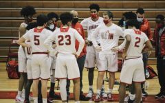 The boys varsity basketball team huddles up during a timeout in their 72-53 win against Mount Vernon.