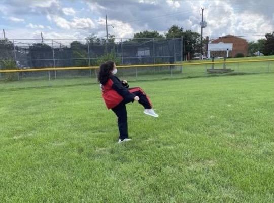 Freshman Sibyl Dauer practices her martial arts skills in an empty field.