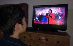 Junior Jin Ho Yoo Rodriguez watches the halftime performance at home.