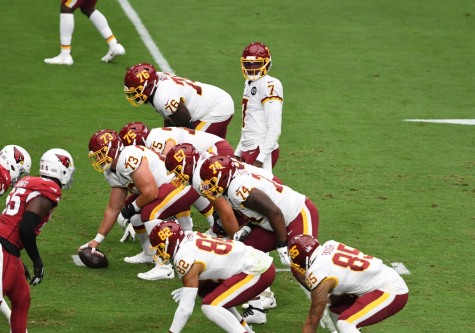 Former Washington Football Team quarterback Dwayne Haskins is under center getting ready for a play. Haskins was cut towards the end of last year