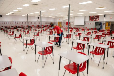 AHS custodial staff members clean and disinfect the cafeteria desks, which were put in to follow social distancing guidelines.