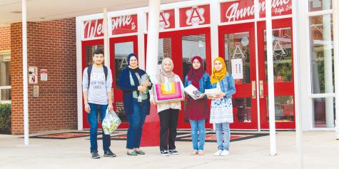 Junior Ahsanullah Luddin, Assistant Principal Sarah Eqab, sophomore Sosan Barakzai, senior Khujasta Basiri and sophomore Husna Basiri stand in front the school.