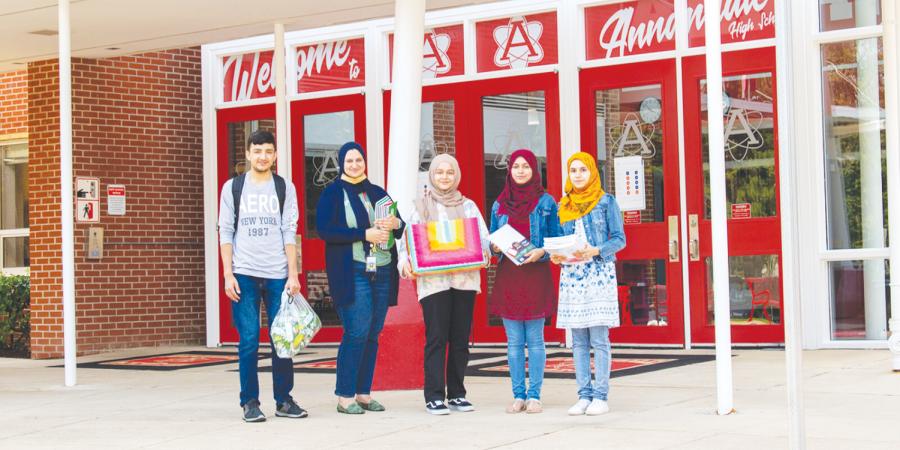 Junior+Ahsanullah+Luddin%2C+Assistant+Principal+Sarah+Eqab%2C+sophomore+Sosan+Barakzai%2C+senior+Khujasta+Basiri+and+sophomore+Husna+Basiri+stand+in+front+the+school.%0A